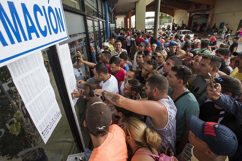 <p>Un grupo de cubanos mira las listas de los primeros afortunados que podrán volar en Estados Unidos.</p>
