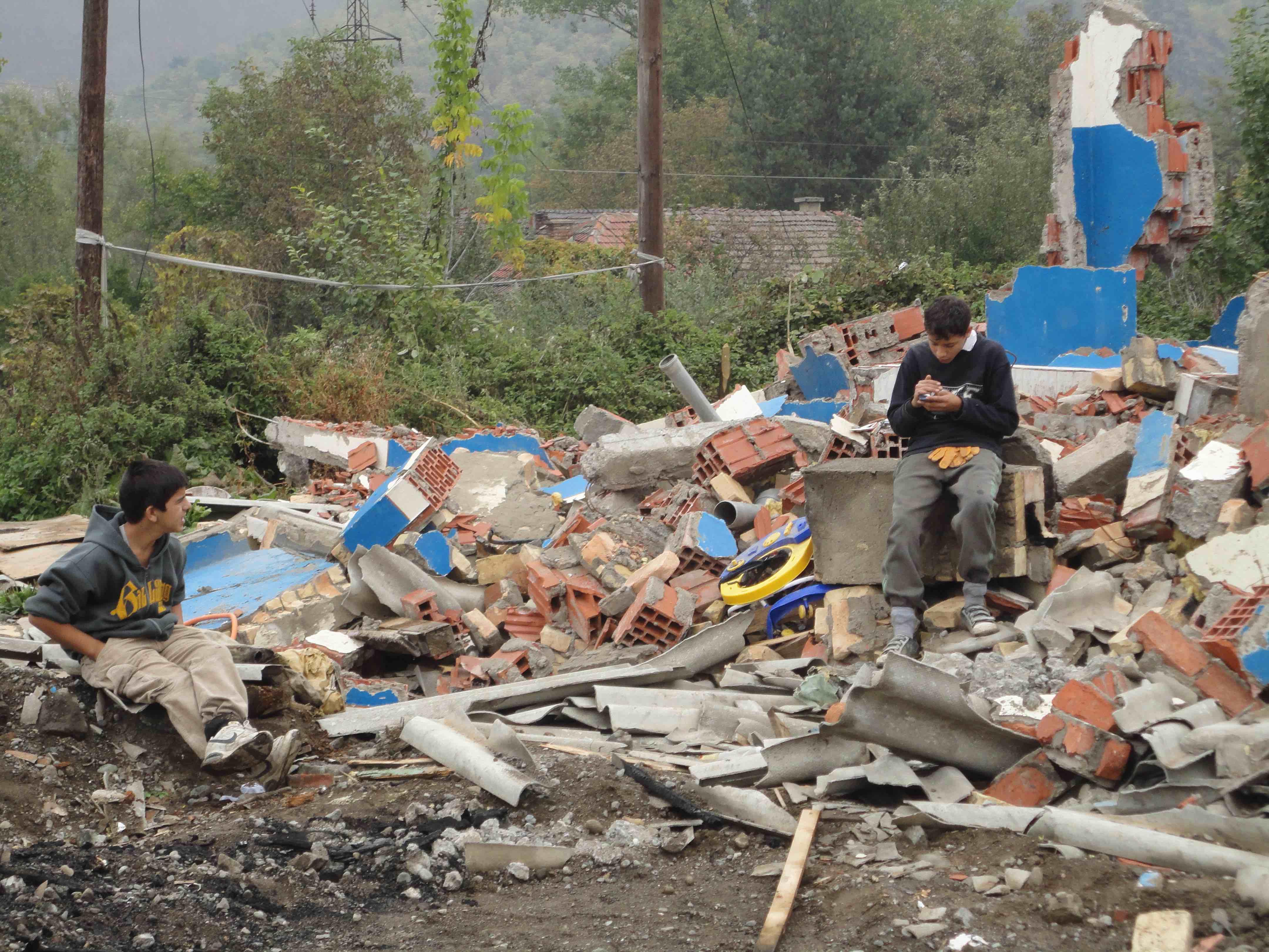 <p>Niños romaníes se toman un descanso tras buscar material que reutilizar en el campo de Cesmin Lug.</p>
