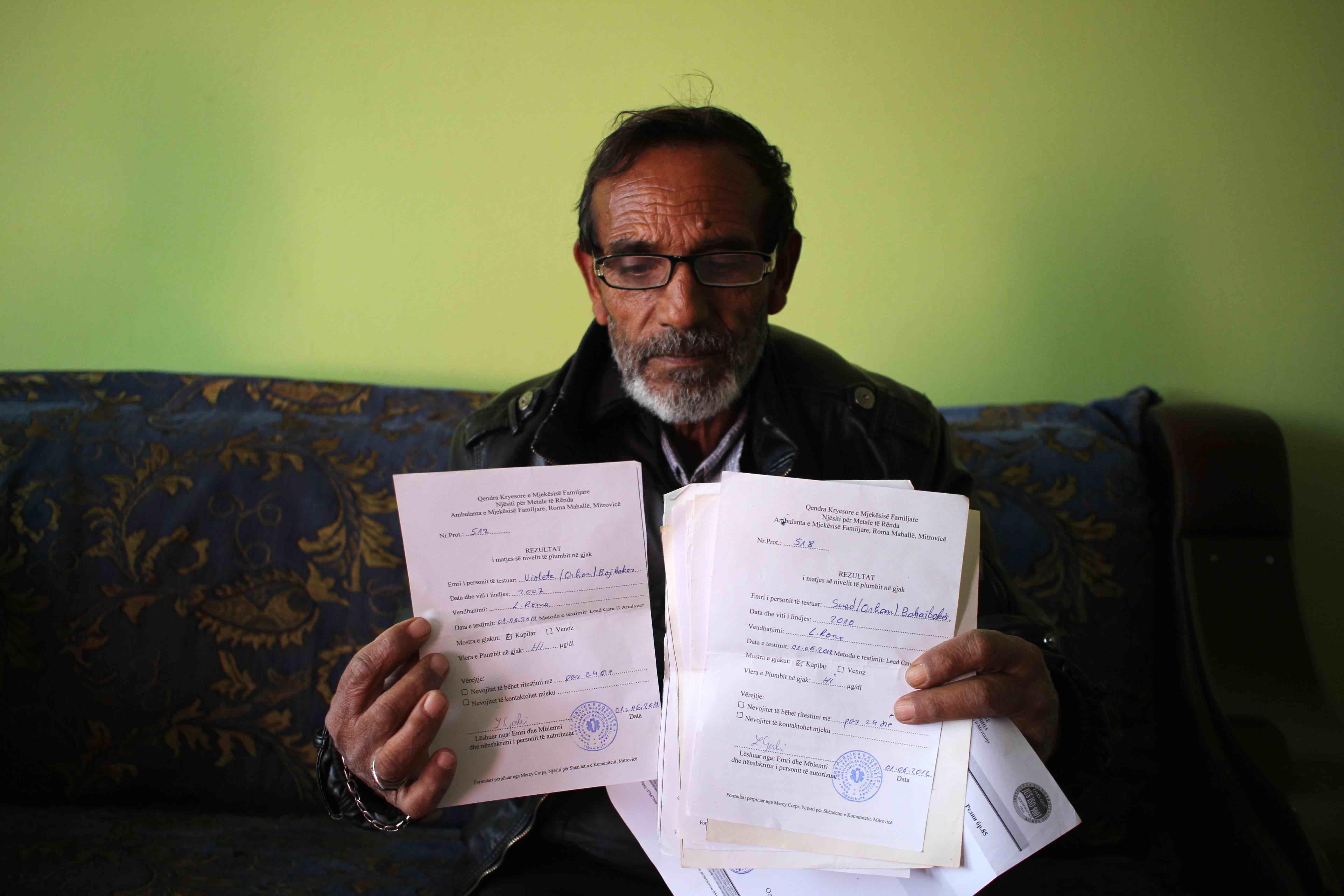<p>Bayram Babajboks sostiene documentos con los resultado de las pruebas médicas de sus nietos.</p>