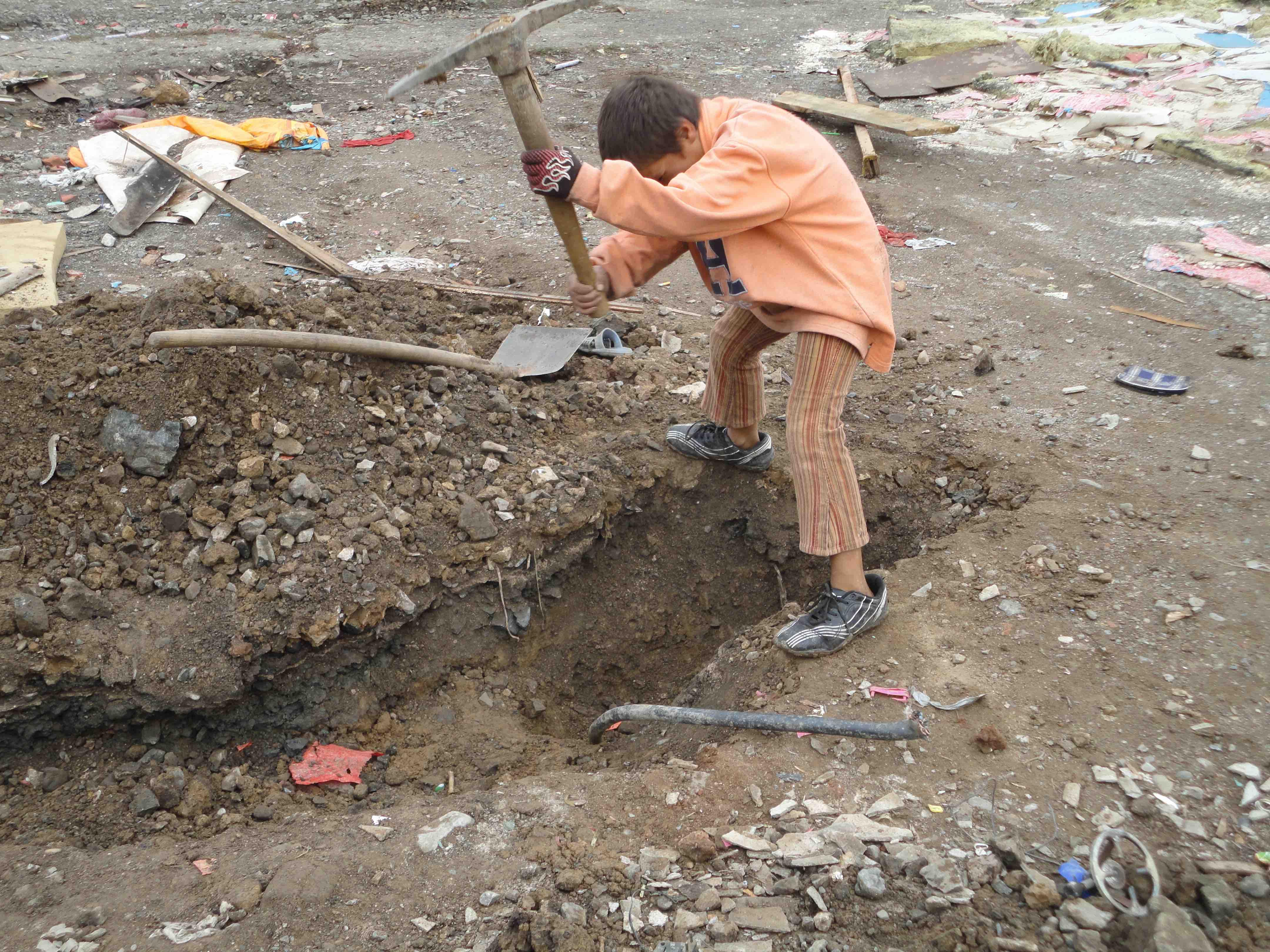 <p>Un niño pica en el suelo para poder extraer el cableado eléctrico del campo de Cesmin Lug.</p>