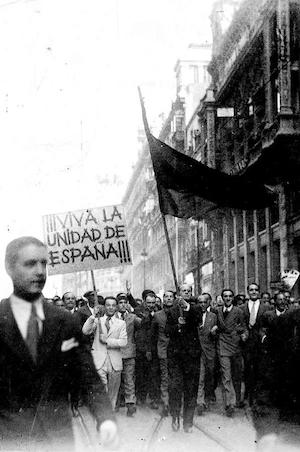 <p>José Antonio Primo de Rivera, al frente de una manifestación contra 'los separatistas catalanes', en la Puerta del Sol (Madrid), el 7 de octubre de 1934. El líder de Falange camina detrás del abanderado.</p>